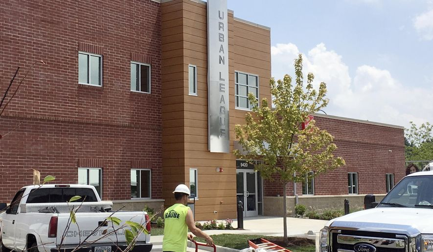 In this Tuesday, July 25, 2017, photo, a construction worker helps with finishing touches at the new Ferguson Empowerment Center in Ferguson, Mo. The new $3 million center will house an Urban League office focused on job training and placement. A dedication ceremony is planned Wednesday morning, July 26. (AP Photo/Jim Salter)