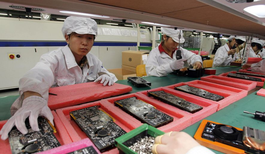 "In this May 26, 2010, file photo, staff members work on the production line at the Foxconn complex in the southern Chinese city of Shenzhen, Southern city in China. Wisconsin Gov. Scott Walker says President Donald Trump plans to make a ""major jobs announcement for Wisconsin"" as anticipation builds it will be about electronics giant Foxconn locating in the state. Taiwan-based Foxconn is best known as the assembler of the iPhone. (AP Photo/Kin Cheung, File)"