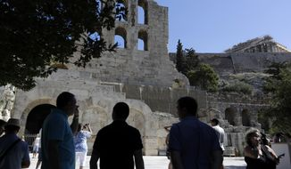 FILE - In this Thursday, July 6, 2017 file photo tourists take photographs the Herod Atticus theater and Parthenon temple atop of Acropolis hill during a three-hour work stoppage in Athens. The culture ministry workers' union said on Wednesday, July 26, 2017 that will go on a two-day strike protesting staff shortages will shut the Acropolis and other ancient sites and museums in Athens this weekend, at the height of the tourist season. (AP Photo/Thanassis Stavrakis, File)