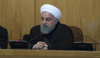 In this photo released by official website of the office of the Iranian Presidency, Iran's President Hassan Rouhani speaks in a cabinet meeting in Tehran, Iran, Wednesday, July 26, 2017. Iran's President Hassan Rouhani says his country will respond if U.S. legislation imposing sanctions on people involved in Iran's ballistic missile program becomes law. (Iranian Presidency Office via AP)