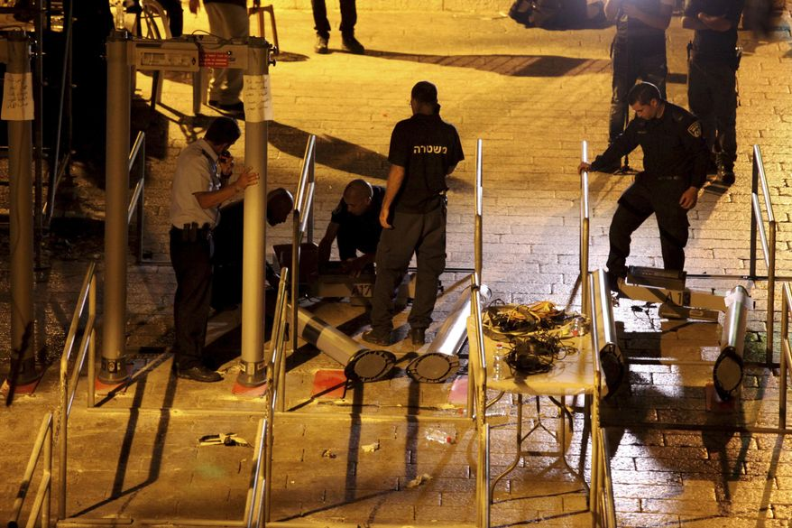 Israeli police officers dismantle metal detectors outside the Al Aqsa Mosque compound in Jerusalem's Old City, early Tuesday, July 25, 2017. Israel's security cabinet has decided to remove metal detectors set up at the entrance to a Jerusalem holy site which had angered Muslims. (AP Photo/Mahmoud Illean)