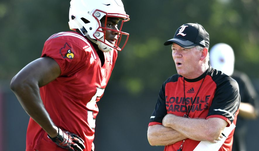 FILE - In this Aug. 5, 2016, file photo, Louisville head football coach Bobby Petrino, right, talks with freshman wide receiver Seth Dawkins as they go through workouts at their first public practice, in Louisville Ky. The Cardinals begin fall practice Monday with holes to fill on both sides of the ball after losing their final three games. (AP Photo/Timothy D. Easley, File)