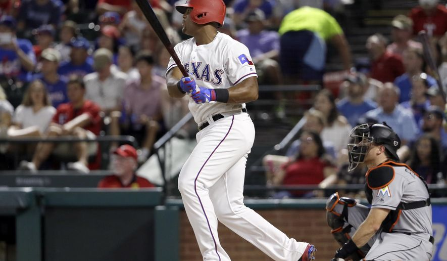 Texas Rangers' Adrian Beltre, left, follows through on a run-scoring double as Miami Marlins' J.T. Realmuto watches in the sixth inning of a baseball game, Wednesday, July 26, 2017, in Arlington, Texas. The hit that scored Nomar Mazara was Beltre's 2,995th career hit. (AP Photo/Tony Gutierrez)
