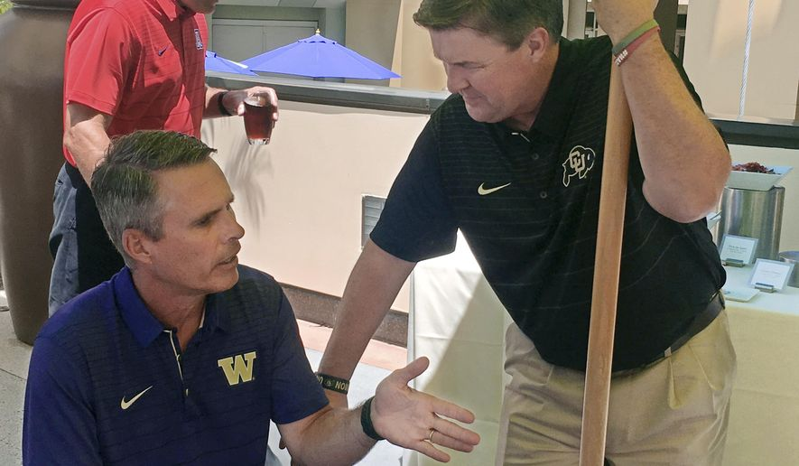 Washington coach Chris Petersen, left, gestures while speaking to Colorado coach Mike MacIntyre at Pac-12 NCAA college football media day, Wednesday, July 26, 2017, in the Hollywood section of Los Angeles. Petersen and MacIntyre both realize it will be difficult to duplicate their unlikely success of last season, when their teams met in the conference's championship game. (AP Photo/Greg Beacham)