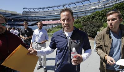 New England Patriots offensive coordinator Josh McDaniels, center, steps away from members of the media after taking questions at NFL football training camp, Wednesday, July 26, 2017, in Foxborough, Mass. (AP Photo/Steven Senne)