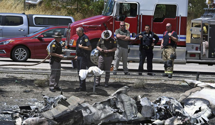 Investigators look over wreckage of a small plane that crashed along Interstate 15 Wednesday, July 26, 2017, near Riverdale, Utah. Authorities say four people died when a small plane crashed on a northern Utah interstate median, tangling traffic and leaving blackened wreckage on the highway. Utah Department of Public Safety officials confirmed the deaths in the Wednesday-afternoon crash north of Salt Lake City, but did not immediately release further information on the deceased or the cause of the crash. No injuries were reported on the ground. (Sarah Welliver /Standard-Examiner via AP)