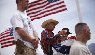 FILE - In this April 18, 2014, file photo, rancher Cliven Bundy, flanked by armed supporters, speaks at a protest camp near Bunkerville, Nev. Gregory Burleson, 53, of Phoenix, was sentenced Wednesday, July 26, 2017, in Las Vegas, Nev., to more than 68 years in federal prison for his role as a gunman in a standoff that stopped federal agents from rounding up cattle near Cliven Bundy's Nevada ranch in 2014. (John Locher/Las Vegas Review-Journal via AP, File)