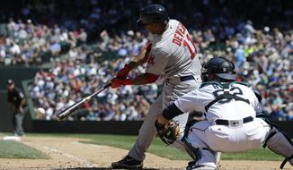 Boston Red Sox's Rafael Devers hits a single in the seventh inning of a baseball game as Seattle Mariners catcher Carlos Ruiz looks on, Wednesday, July 26, 2017, in Seattle. (AP Photo/Ted S. Warren)