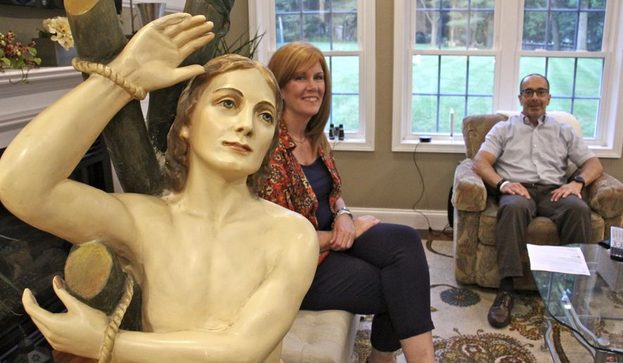 In this June 14, 2017, photo provided by WHYY, Ed and Kathleen Nader sit in their living room in Exton, Pa, with a statue of St. Pantaleon that has been in Ed's family for four generations. The nearly life-sized statue missing for decades from an Italian church is being returned by the American couple, who finally solved the mystery of their family's odd relic. (Emma Lee/WHYY via AP)