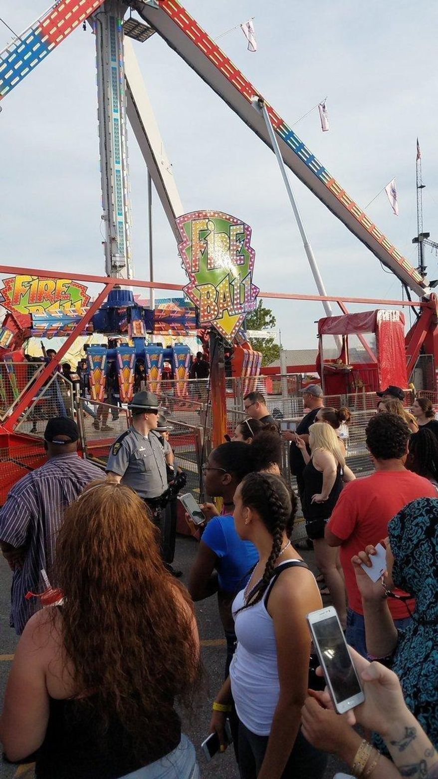 People watch as authorities respond near the Fire Ball amusement ride after the ride malfunctioned injuring several at the Ohio State Fair, Wednesday, July 26, 2017, in Columbus, Ohio. Some of the victims were thrown from the ride when it malfunctioned Wednesday night, said Columbus Fire Battalion Chief Steve Martin. (Justin Eckard via AP)