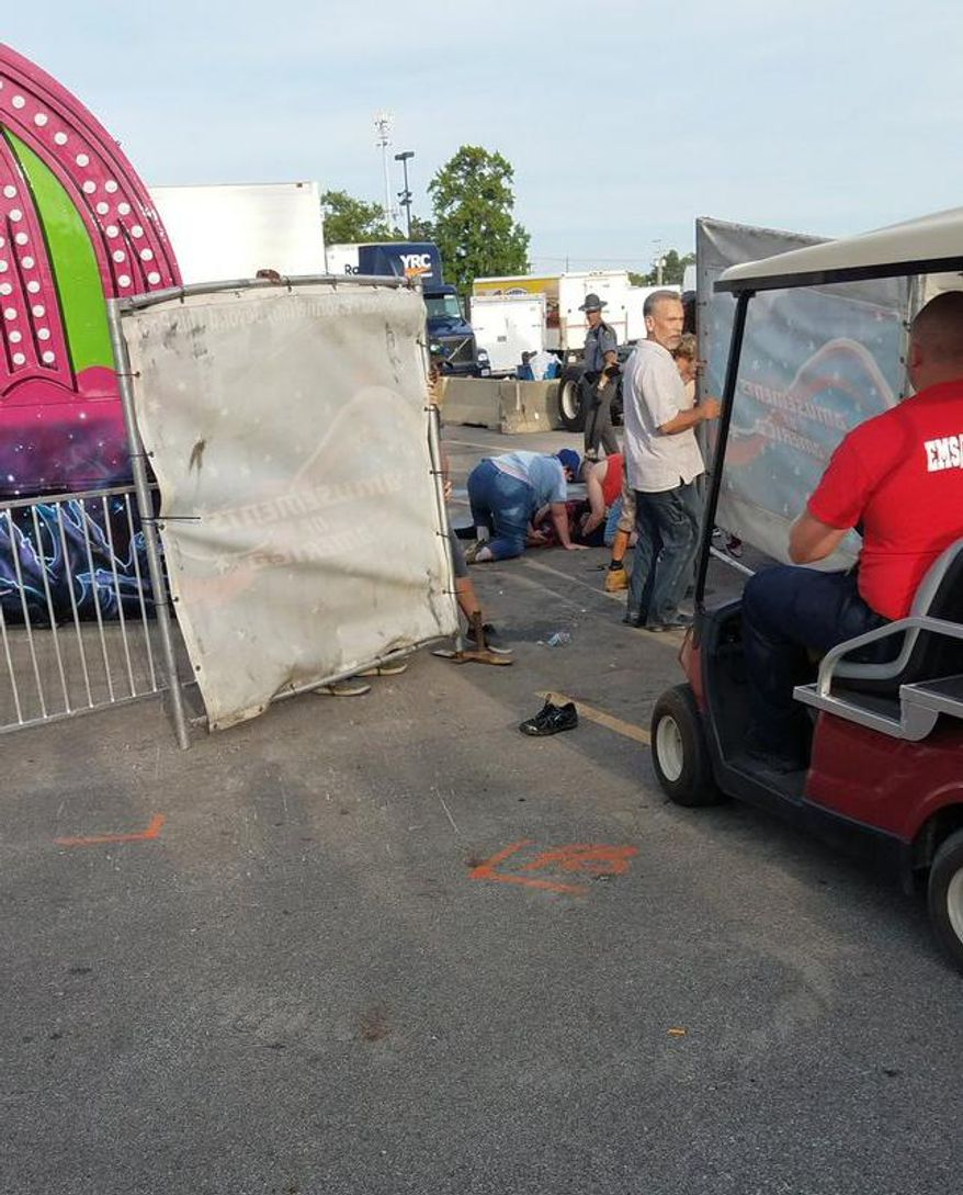 A person is attended to as authorities respond after the Fire Ball amusement ride malfunctioned injuring several at the Ohio State Fair, Wednesday, July 26, 2017, in Columbus, Ohio. Some of the victims were thrown from the ride when it malfunctioned Wednesday night, said Columbus Fire Battalion Chief Steve Martin. (Justin Eckard via AP)