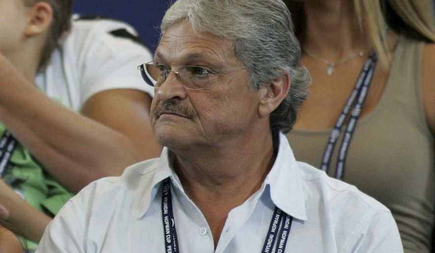 FILE - In this Jan. 3, 2005, file photo, Nikolaos Philippoussis sits in the stands watching his son, Mark Philippoussis, play in the Hopman Cup tennis tournament in Perth, Australia. A San Diego County sheriff's official says the father of a retired Australian tennis star has been arrested on suspicion of molesting two children, the San Diego Union-Tribune reports. The newspaper says Nikolaos Philippoussis, 68, a tennis coach, was taken into custody at his home on Tuesday, July 25, 2017. The Union-Tribune reports that officials said the two victims were under age 14 and were students of Philippoussis. Mark Philippoussis was once ranked eighth in the world. (AP Photo/Mark Ralston, File )