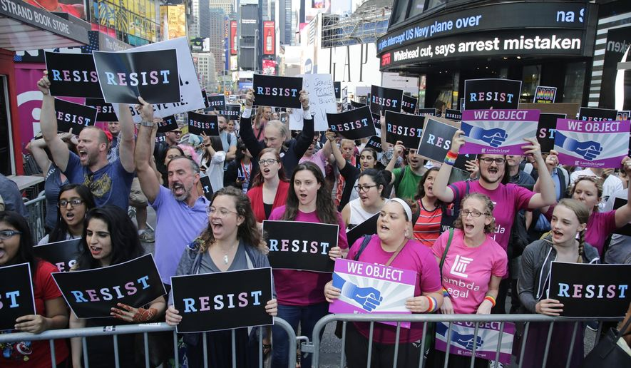 "Protestors gather in Times Square, Wednesday, July 26, 2017, in New York. President Donald Trump declared a ban Wednesday on transgender troops serving anywhere in the U.S. military, catching the Pentagon flat-footed and unable to explain what it called Trump's ""guidance."" His proclamation, on Twitter rather than any formal announcement, drew bipartisan denunciations and threw currently serving transgender soldiers into limbo. (AP Photo/Frank Franklin II)"