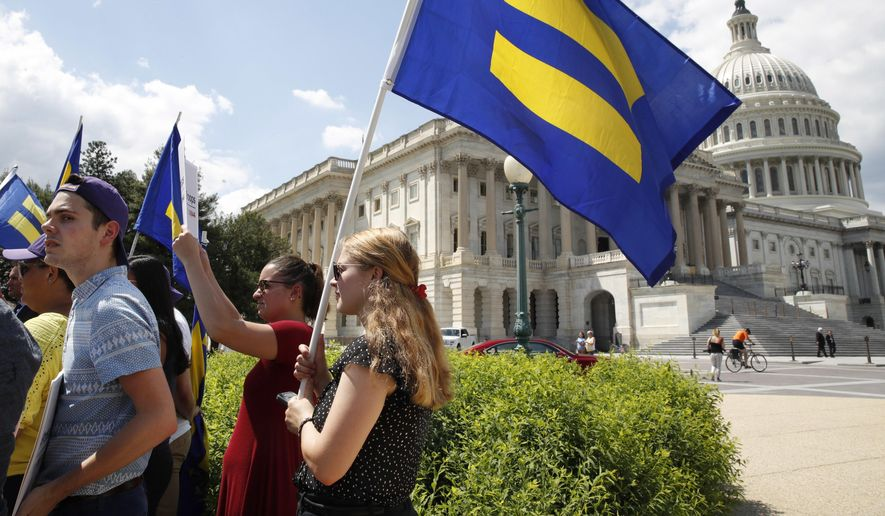 """Demonstrators displayed """"equality"""" flags on Capitol Hill during an event held by Rep. Joe Kennedy, Massachusetts Democrat, in support of transgender members of the military, in response to President Trump's declaration Wednesday that he wants transgender people barred from service. (Associated Press)"""