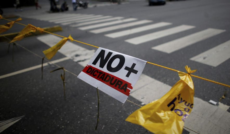 "A sign with a message that reads in Spanish: ""No more dictatorship"" is attached to a rope formig part of a barricade made by demonstrators during a 48-hour general strike beginning Wednesday in protest of government plans to rewrite the constitution in Caracas, Venezuela, Wednesday, July 26, 2017. Streets were quiet Wednesday morning in much of the capital, Caracas, as many residents stayed home in observance of the strike. (AP Photo/Ariana Cubillos)"