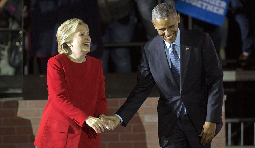 President Barack Obama and Democratic presidential candidate Hillary Clinton hold hands as they walk off stage after both spoke at a rally at Independence Mall in Philadelphia. Monday, Nov. 7, 2016. (AP Photo/Pablo Martinez Monsivais)