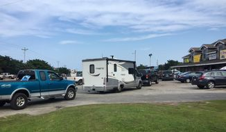 Vehicles line up at the a gas station on Thursday, July 27, 2017, on Ocracoke Island on North Carolina's Outer Banks, as visitors leave the island and residents fuel up. An estimated 10,000 tourists were ordered Thursday to evacuate the island after a construction company caused a power outage, leaving people stranded without air conditioning or places to eat. (C. Leinbach/Ocracoke Observer via AP)