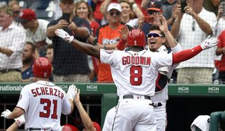 Washington Nationals' Brian Goodwin celebrates his two-run home run with Jose Lobaton, right, during the third inning of a baseball game against the Milwaukee Brewers, Thursday, July 27, 2017, in Washington. Nationals' Max Scherzer (31) who scored on the play, is greeted at the dugout. (AP Photo/Nick Wass)