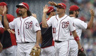 Washington Nationals' Ryan Zimmerman (11) and Anthony Rendon (6) and others celebrate their 15-2 win over the Milwaukee Brewers in a baseball game, Thursday, July 27, 2017, in Washington. (AP Photo/Nick Wass)
