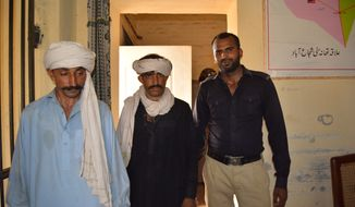 Unidentified members of a village council stand with a police officer, right, at a police station in Muzaffarabad, Pakistan, Thursday, July 27, 2017. Police on Thursday arrested the head of a village council in central Pakistan for allegedly sanctioning the rape of a teenage girl, a police spokeswoman said, as Amnesty International demanded ban on such councils. (AP Photo/Arif Ali)