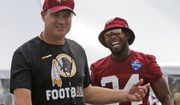 Washington Redskin head coach, Jay Gruden, left, jokes with corner back Josh Norman, right, as the arrive at the start of the Washington Redskins NFL training camp in Richmond,. Va., Thursday, July 27, 2017. (AP Photo/Steve Helber)
