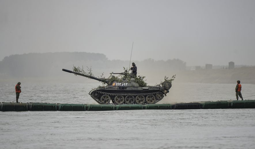 A Romanian army tank maneuvers on a pontoon bridge on Borcea tributary to the Danube river during the Saber Guardian 17 joint military exercise with US troops, in Bordusani, Ialomita, Romania, Sunday, July 16, 2017. The Saber Guardian 17 exercises led by U.S. Army Europe began this week in Eastern Europe involving 25,000 military personnel from more than 20 allied and partner countries. (AP Photo/Andreea Alexandru)