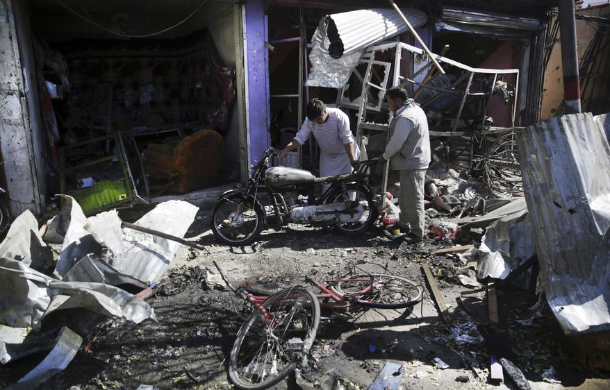 FILE - In this Monday, July 24, 2017 file photo, Men look at the remains of their properties at the site of a suicide attack in Kabul, Afghanistan. In the last week the Taliban have overrun two districts in the north and west of Kabul, temporarily cut a key highway linking the capital to the north and staged a suicide bombing in the heart of the capital Kabul. (AP Photos/Massoud Hossaini, File)
