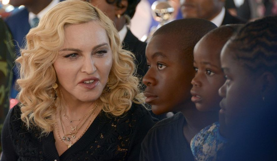 """FILE- In this July 11, 2017 file photo, Madonna, left, sits with her adopted children David, Stella and Mercy, at the opening of The Mercy James Institute for Pediatric Surgery and Intensive Care, located at the Queen Elizabeth Central Hospital in the city of Blantyre, Malawi. A lawyer for Madonna said Thursday July 27, 2017, that the star and her twin daughters Stella and Estere have accepted damages form the publisher of the Mail Online website over an article that was a """"serious invasion of privacy."""" Madonna sued Associated Newspapers over a January story giving details of her adoption of the 4-year-old twins from Malawi.  (AP Photo Thoko Chikondi, File)"""