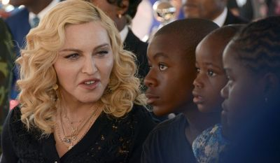 "FILE- In this July 11, 2017 file photo, Madonna, left, sits with her adopted children David, Stella and Mercy, at the opening of The Mercy James Institute for Pediatric Surgery and Intensive Care, located at the Queen Elizabeth Central Hospital in the city of Blantyre, Malawi. A lawyer for Madonna said Thursday July 27, 2017, that the star and her twin daughters Stella and Estere have accepted damages form the publisher of the Mail Online website over an article that was a ""serious invasion of privacy."" Madonna sued Associated Newspapers over a January story giving details of her adoption of the 4-year-old twins from Malawi.  (AP Photo Thoko Chikondi, File)"