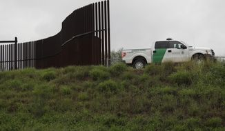 FILE - In this Nov. 13, 2016 file photo, a U.S. Customs and Border Patrol agent passes along a section of border wall in Hidalgo, Texas. The GOP-controlled House is plowing ahead on legislation to give the Pentagon a massive spending boost and deliver a $1.6 billion down payment for President Donald Trump's oft-promised wall along the U.S.-Mexico border. (AP Photo/Eric Gay, File)