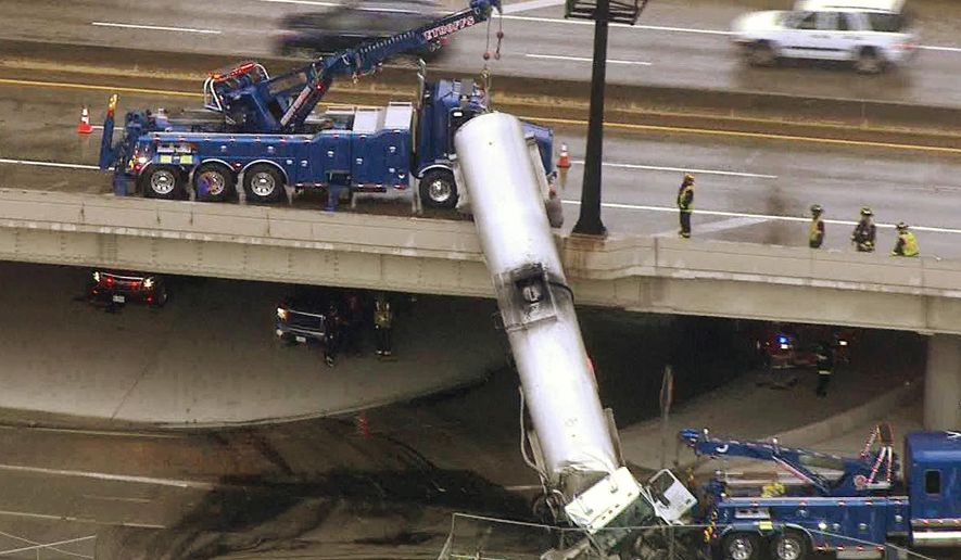 In this photo from video provided by KMOV-TV, emergency responders work to lower a tanker truck to the ground after it crashed off an Interstate 44 overpass in downtown St. Louis, Thursday, July 27, 2017. (KMOV-TV via AP)