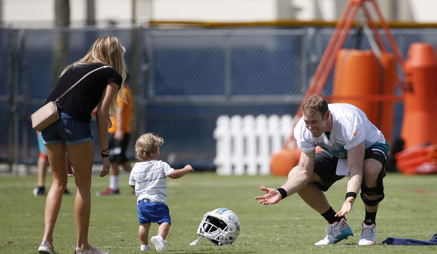 Miami Dolphins quarterback Ryan Tannehill, right, crouches down as his son Steel Ryan and wife Lauren run to him after NFL football training camp, Thursday, July 27, 2017, at the team's training facility in Davie, Fla. (AP Photo/Wilfredo Lee)