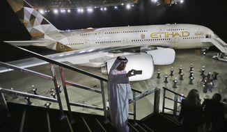 FILE- In this Thursday, Dec. 18, 2014 file photo, an Emirati man takes a selfie in front of a new Etihad Airways A380 in Abu Dhabi, United Arab Emirates. Etihad, the flag carrier of the United Arab Emirates, said Thursday, July 27, 2017 it lost $1.87 billion in 2016. (AP Photo/Kamran Jebreili, File)
