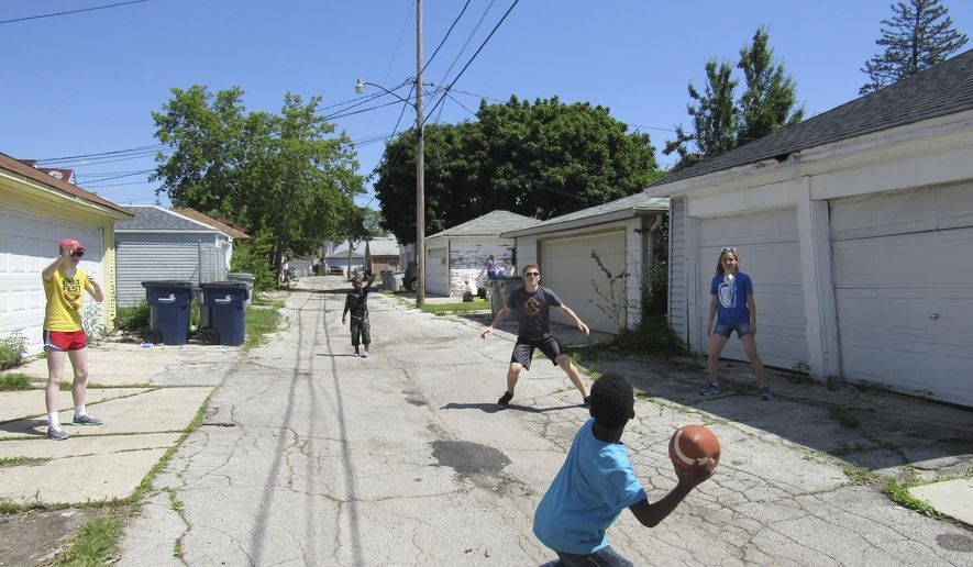 This June 27, 2017 photo shows a team of workers from the youth group  Asbury United Methodist Church play football with local children in Milwaukee. A week-long mission trip to Milwaukee for the youth group at Asbury United Methodist Church in Madison wasn't just about scraping, painting and weeding. The trip also allowed for interaction with children from the neighborhood.  (Barry Adams/Wisconsin State Journal via AP)