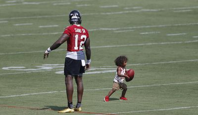 Atlanta Falcons wide receiver Mohamed Sanu (12) plays with his son, Mohamed Jr., after the first day of an NFL training camp football practice Thursday, July 27, 2017, in Flowery Branch, Ga. (AP Photo/John Bazemore)