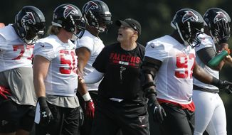Atlanta Falcons head coach Dan Quinn works with his defensive line during NFL football training camp Thursday, July 27, 2017, in Flowery Branch, Ga. (AP Photo/John Bazemore)