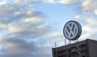 FILE - In this Sept. 26, 2015 file photo a giant logo of the German car manufacturer Volkswagen is pictured on top of a company's factory building in Wolfsburg, Germany. Volkswagen will announce its second-quarter earnings on Thursday, July 27, 2017. (AP Photo/Michael Sohn, file)