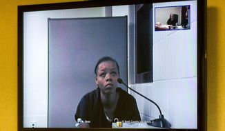 Lovily Kristine-Anwonette Johnson  appears on a video monitor for her arraignment at Wyoming District Court on Monday, July 24, 2017 in Wyoming, Mich. Court records say Johnson was charged with first-degree murder and first-degree child abuse in the death of 6-month-old Noah Johnson.  (Cory Morse/The Grand Rapids Press via AP)