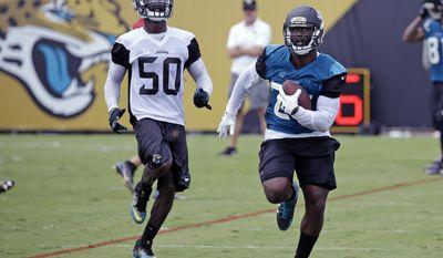 Jacksonville Jaguars running back Leonard Fournette, right, gets past linebacker Telvin Smith (50) during a drill at NFL football training camp, Thursday, July 27, 2017, in Jacksonville, Fla. (AP Photo/John Raoux)