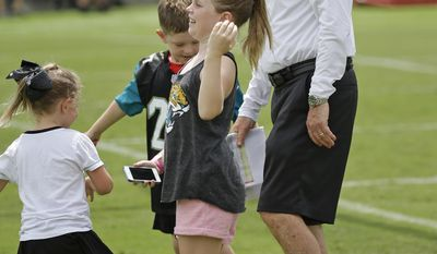 Tom Coughlin, right, executive vice president of football operations for the Jacksonville Jaguars, is greeted by several of his grandchildren during a break at NFL football training camp, Thursday, July 27, 2017, in Jacksonville, Fla. (AP Photo/John Raoux)