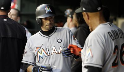 Miami Marlins' Ichiro Suzuki, left, of Japan is congratulated by outfield/base running coach Lorenzo Bundy, right, after Suzuki and J.T. Realmuto scored on a Derek Dietrich single in the fourth inning of a baseball game against the Texas Rangers on Wednesday, July 26, 2017, in Arlington, Texas. (AP Photo/Tony Gutierrez)
