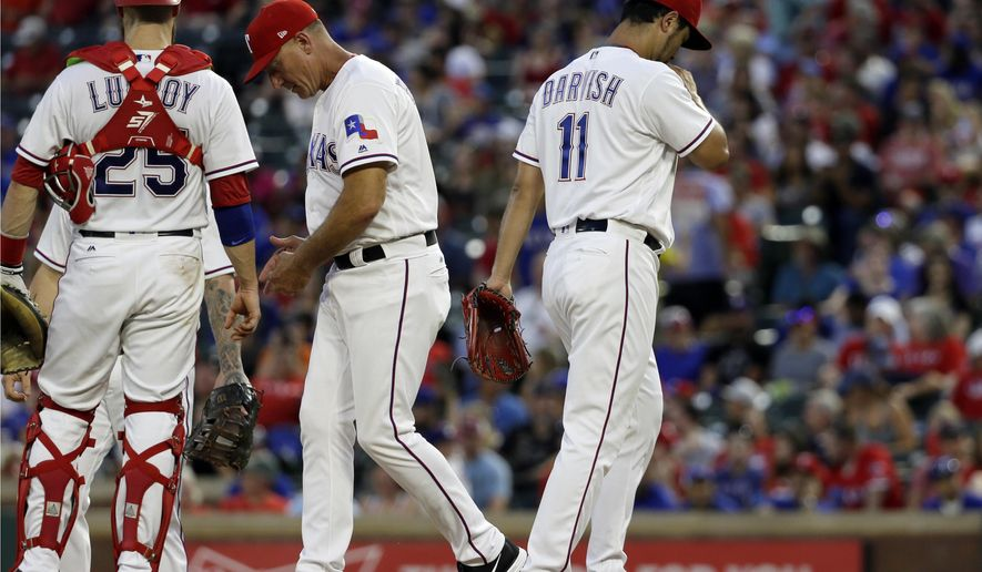 Texas Rangers' Jonathan Lucroy stands on the mound after manager Jeff Banister, center, took the ball from starting pitcher Yu Darvish of Japan in the fourth inning of a baseball game against the Miami Marlins on Wednesday, July 26, 2017, in Arlington, Texas. (AP Photo/Tony Gutierrez)