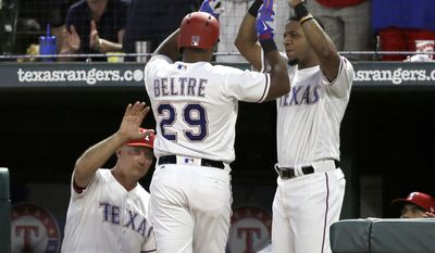 Texas Rangers' Jeff Banister, left, and Elvis Andrus, right, congratulate Adrian Beltre (29) after Beltre hit a solo home run off a pitch from Miami Marlins starter Jose Urena in the fourth inning of a baseball game, Wednesday, July 26, 2017, in Arlington, Texas. (AP Photo/Tony Gutierrez)