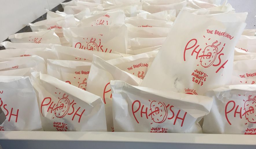 "In this July 26, 2017 photo, bags of doughnuts are prepared to be handed out to fans of the band Phish in New York. The band is handing doughnuts out at its ""Baker's Dozen"" residency at New York's Madison Square Garden. (AP Photo/Josh Cornfield)"