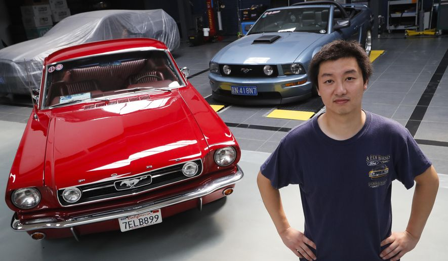 In this Wednesday, June 28, 2017, photo, Guo Xin poses with his 1966 MT GT Fastback, left, and 2005 GT convertible at his garage in Beijing. A former race car driver, Guo finds Mustangs tougher and more fun to drive than European or Japanese sports cars. (AP Photo/Andy Wong)