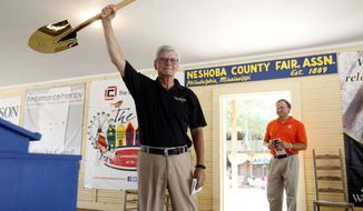 Mississippi Republican Gov. Phil Bryant shows off a gold shovel he was awarded for the state's economic progress as he leaves the stage at the Neshoba County Fair in Philadelphia, Miss., Thursday, July 27, 2017. Bryant says employees at the Nissan Motor Co. plant in Mississippi should reject unionization. Workers at the manufacturing plant in Canton will vote Aug. 3 and 4 on whether to affiliate with the United Auto Workers. The union is trying to win its first vote at an entire plant in the South. (AP Photo/Rogelio V. Solis)
