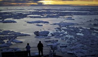 Researchers look out from the Finnish icebreaker MSV Nordica as the sun sets over sea ice floating on the Victoria Strait along the Northwest Passage in the Canadian Arctic Archipelago, Friday, July 21, 2017. Sea ice plays an important role in the global climate system by cooling the surrounding water and air. It helps maintain ocean and atmospheric currents that affect weather which is characteristic for certain parts of the world, such as the comparatively mild temperatures found in western Europe. (AP Photo/David Goldman) **FILE**