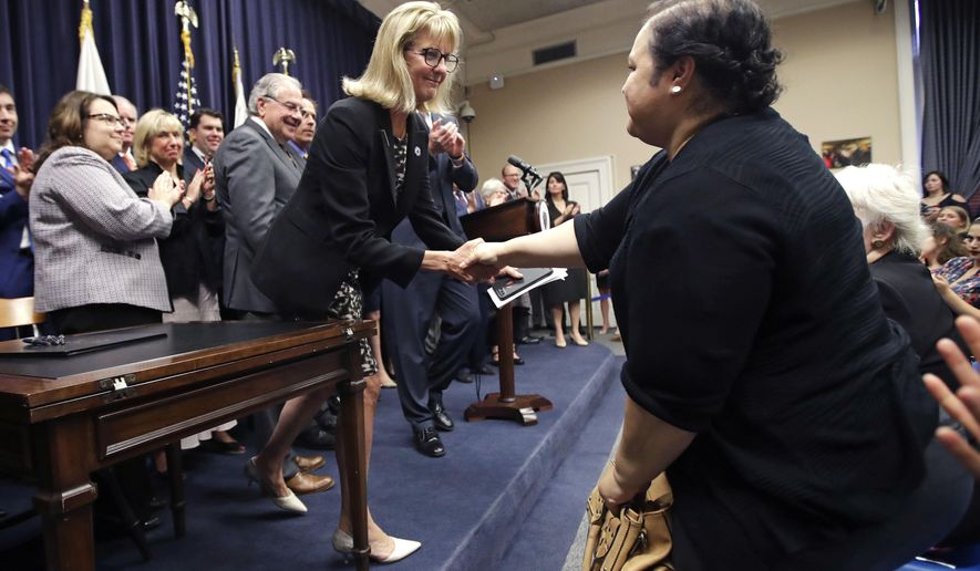 Mass. Sen. Joan Lovely, D-Salem, left, shakes hands with Alejandra Duarte after the Pregnant Workers Fairness Act was signed into law at the Statehouse, Thursday, July 27, 2017, in Boston. Duarte testified before the legislature during April that she was forced to work longer hours with an increased workload after disclosing to her former employer that she was pregnant and wanted a lighter workload, while working at a Worcester laundry. (AP Photo/Charles Krupa)