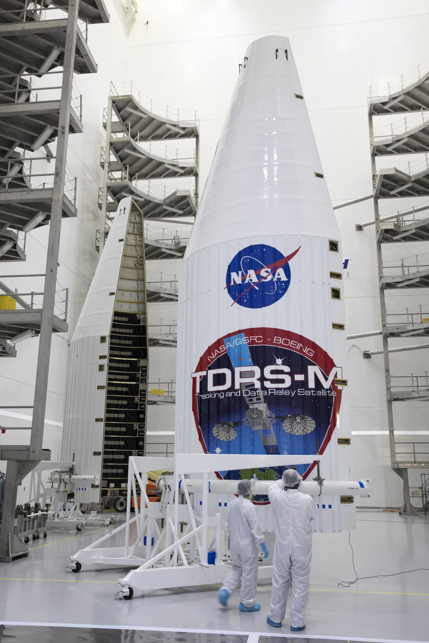 FILE - In this July 13, 2017, file photo provided by NASA, the payload fairing for NASA's Tracking and Data Relay Satellite, TDRS-M, is inspected prior to encapsulating the spacecraft, inside the Astrotech facility in Titusville, Fla. One of the antennas on the Tracking and Data Relay Satellite ended up broken earlier this month during final launch preps causing NASA to delay the launch by more than two weeks. Liftoff is now targeted for Aug. 20 from Cape Canaveral, Fla. (Glenn Benson/NASA via AP, File)