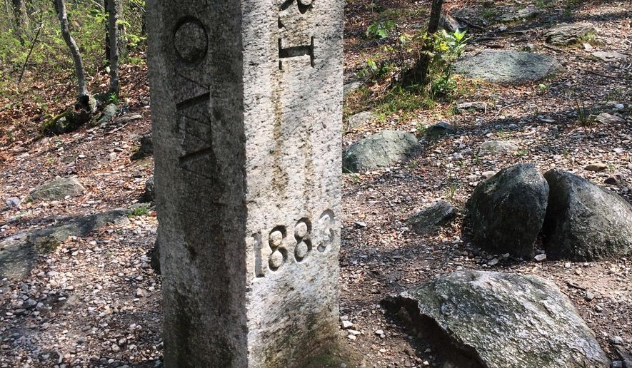 This July 12, 2017 photo shows the granite monument that marks the spot where Connecticut, Massachusetts and Rhode Island meet in Thompson, Conn. There's an unusual travel hobby that has people visiting the woods of Thompson, and other remote spots across the country. The visitors are looking for tripoints, spots where three states meet. (AP Photo/Pat Eaton-Robb)
